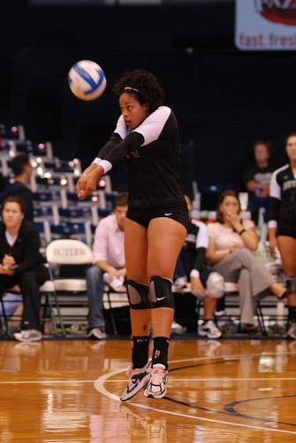 In serve receive, pass with both feet on the court floor rather than doing the
