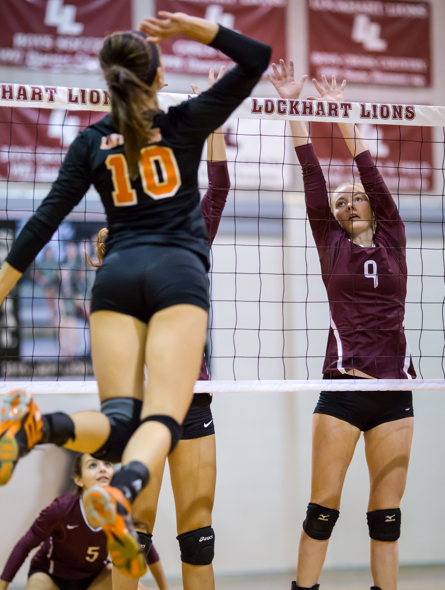 Varsity high school middle watches the hitter while blocking in volleyball game. (Ralph Arvesen)
