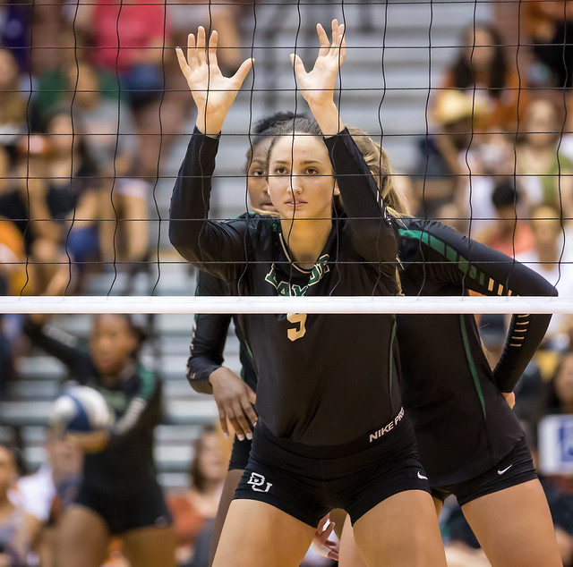What's the block in volleyball? Baylor Bears middle in ready position with hands up at the net ready to block in volleyball defense before the whistle (Ralph Arvesen)