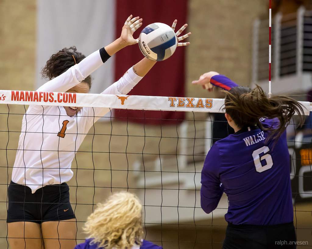 Texas Micaya White gets head and shoulders over the net to stuff block, timing her jump while reading the hitter leaving the hitter no where to go but into the block. (Ralph Arvesen)