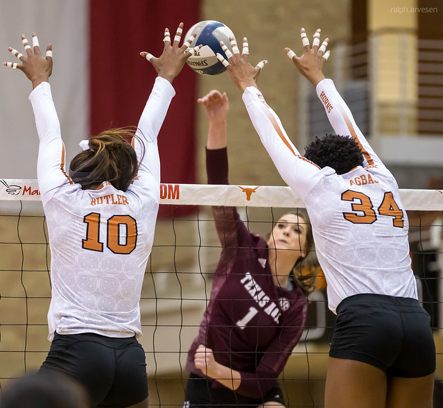 How to spike a volleyball: Texas A&M volleyball hitter aims for the seam of the Texas double block while attacking the ball. (Ralph Aversen)