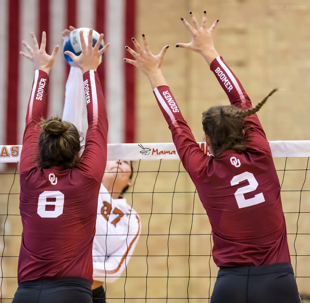Oklahoma Sooners middle blocker (#2) travels laterally across the net to close the seam between her and her outside hitter volleyball player (#8) (Ralph Arvesen)