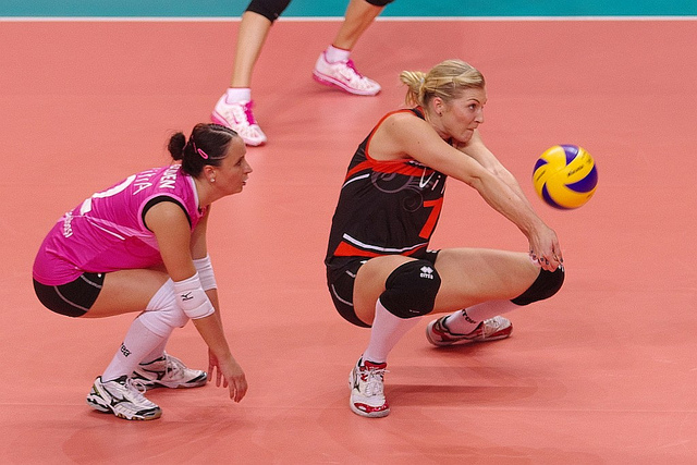 Forearm pass a volleyball with hips below the ball, thumbs pointed to the ground creating a straight armed platform while watching the ball contact the arms. (Jaroslaw Popczyk)