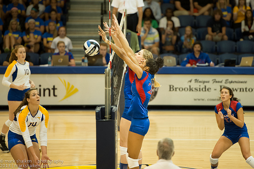 Kansas Bluejays volleyball team double blocks at the net during Big 12 Conference competition.