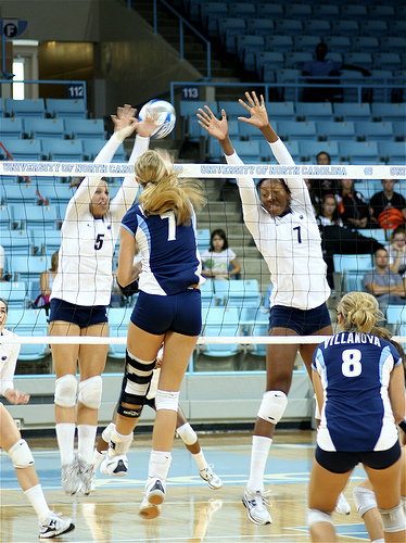 Tips On Volleyball Hitting: Why Hitters Change Up Their Attack: Villanova powers a strong volleyball hit through the North Carolina seam in the block. (Charlie J)