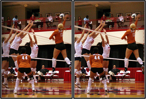 The Houston middle blocker at the peak of her jump penetrates the net with her arms sealing the net. The outside blockers help out in the middle against the Texas middle attack. (Michael E. Johnston)