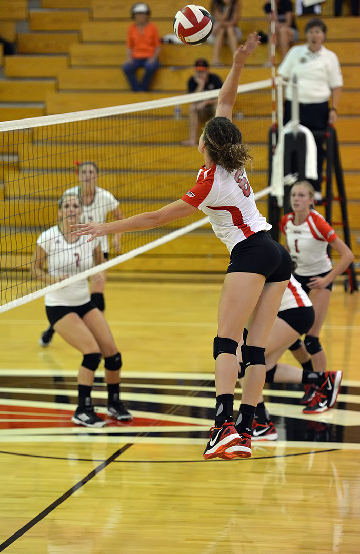 The four-step approach gives outside hitters more time to get to balls that are set higher and are slower to get to the outsides of the net.  Liz Madden spikes a ball from the middle (Al Case)