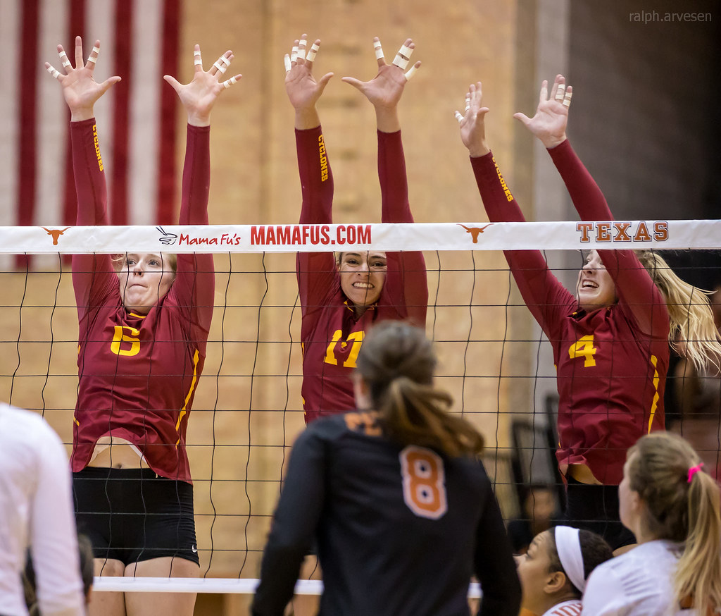 The Middle Volleyball Blocker: Iowa State triple block with middle blocker  (#11) watching the opposing team's hitter. (Ralph Arvesen)