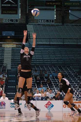 A setter in volleyball uses specific hand and body positioning to deliver a hittable ball to their attackers.