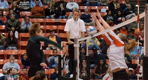 Volleyball officials: First referee calls the game from an elevated referee stand while officiating the two teams competing against each other.