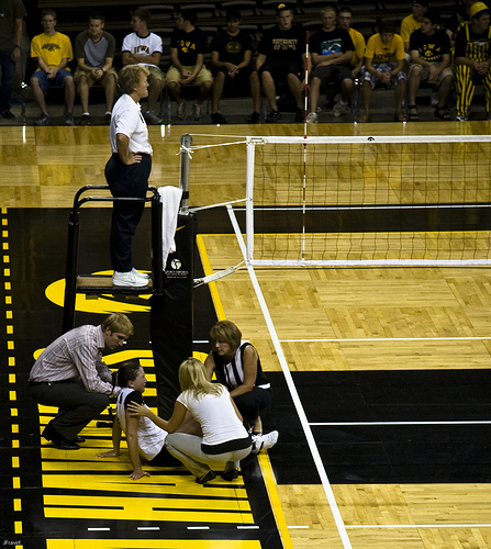 Volleyball officials:First referee waits while an injured players gets attended to.