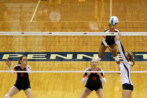 The setter indicates to each of their hitters, before the opposing team serves the ball, what set she plans to deliver to each of them. Illini volleyball setter sets outside (Richard Yuan)