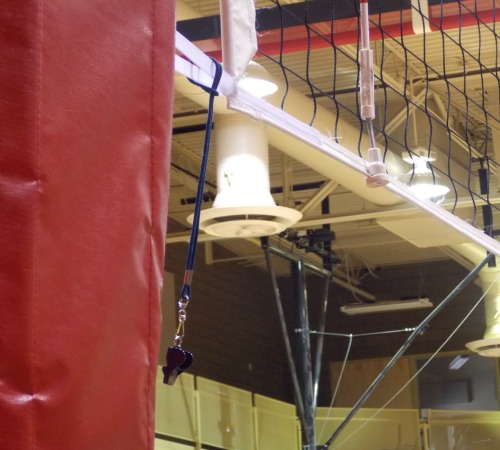 The volleyball antenna base? They are attached to the net and represent a vertical extension of the sideline of that extends up above them to the ceiling and below them to the floor.