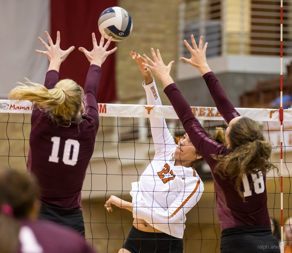 Texas A&M blockers take cross court against the Texas Longhorn outside hitter (Ralph Arvesen)