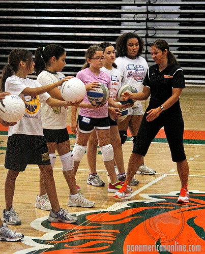 Basic volleyball rules: Young players learning how to serve at camp.