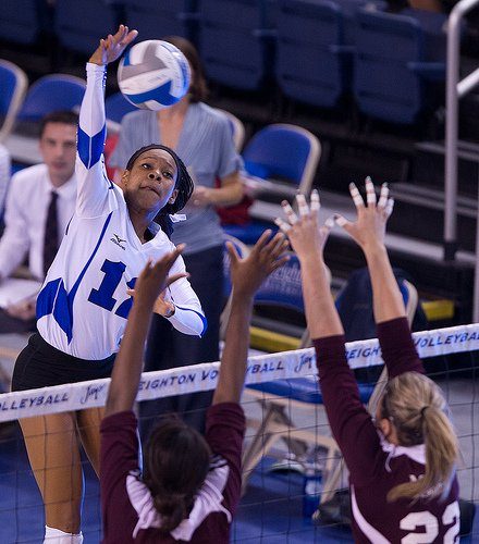 How to Set in Volleyball: When an outside hitter goes up to hit, they usually have two blockers go up in front of them to try and stop them from hitting into their court. (White and Blue Review)