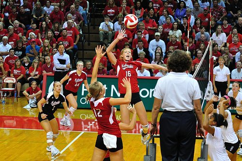 (John Carrel) Front row Nebraska setter runs a quick attack to her middle blocker while opposing team blockers wait and watch.