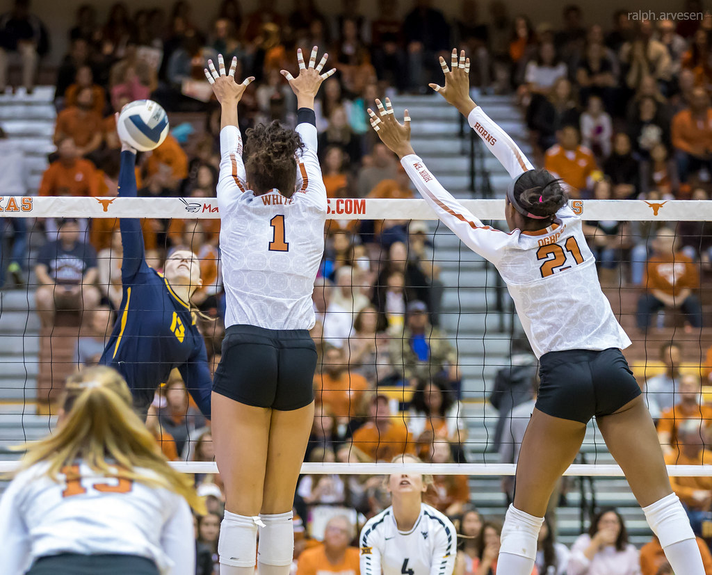 Texas middle blocker (#21) closes the block covers holes between her and outside blocker (Micaya White #1) making it difficult for the opposing hitter to hit the ball between them. (Ralph Arvesen)