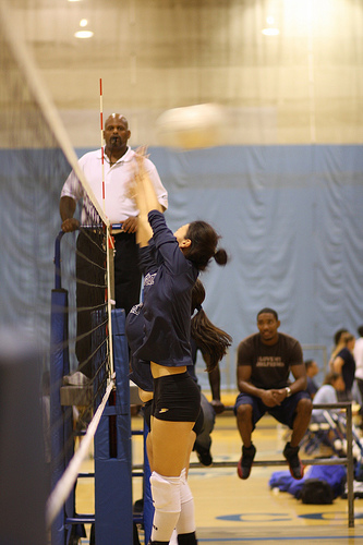 Basic Volleyball Rules: The first referee calls the game from an elevated stand watching for common volleyball faults, calls volleyball fouls, assigns points and sideouts.